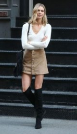 Model Karli Kloss street style – ivory V-neck sweater, camel A-line skirt and black suede over the knee boots…perfect casual look!