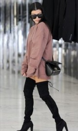 Kourtney Kardashian winter street style…rose-pink oversized sweatshirt and black over the knee boots