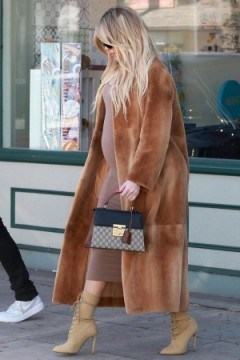 Khloe Kardashian carrying small black and brown handbag, GUCCI Padlock GG Supreme top handle bag, out in Los Angeles, 21 February 2018. - flipped