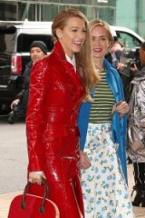 Blake Lively wearing a shiny red trench with Emily Blunt at the Michael Kors show during NYFW, Feb 2018.