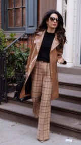 Amal Clooney street style, camel leather trench, black fine knit sweater and brown check wide leg trousers
