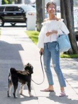 Jamie Chung looking sunny in Los Angeles wearing a white frill neckline bardot top, distressed step hem jeans, pink pointy flats, mirror aviator sunnies and carrying a pastel-blue tote. Celebrity outfits | boho street style