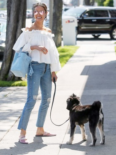 Jamie Chung looking sunny in Los Angeles wearing a white frill neckline bardot top, distressed step hem jeans, pink pointy flats, mirror aviator sunnies and carrying a pastel-blue tote. Celebrity outfits | boho street style - flipped