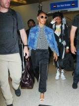 Jada Pinkett Smith's travel style…blue denim jacket worn over a monochrome spot print shirt, black luxe joggers, white barely there sandals and a pair of white framed sunnies. Celebrity airport outfits | star style fashion
