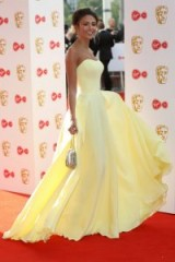 Michelle Keegan on the red carpet wearing a lemon-yellow strapless gown, attending the 2018 BAFTA TV Awards – celebrity style – glamorous events