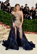 Wearing a stunning statement gown by Versace, model Gigi Hadid did the right thing by keeping her hair in a smooth, simple style which was clipped back behind her ears | celebrity glamour