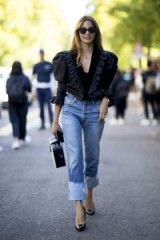 black ruffled leg of mutton sleeve blouse, straight leg jeans with deep turn-ups and high heeled pumps | Milan denim street style