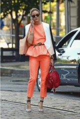 Olivia Palermo in a sleeveless orange peplum top and matching tapered crop-leg pants