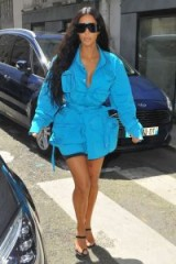 Kim Kardashian wearing a turquoise-blue Louis Vuitton shirt, worn over lycra cycling shorts, Yeezy rubberized leather minimal sandals (available from farfetch.com) and large sunnies | celebrity street style | best Kardashian's look