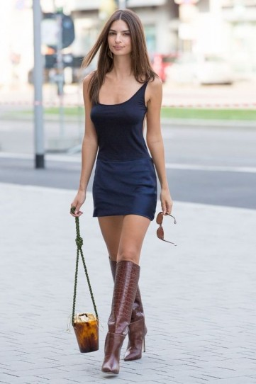 Emily Ratajkowski in a pair of brown leather croc embossed knee high boots and navy slip dress