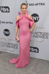 Emily Blunt attending the 2019 SAG Awards, chose a glamorous bubble-gum pink sequinned Michael Kors Collection gown with exaggerated, showy ruffles on the shoulders, and opted for silver-toned accessories.