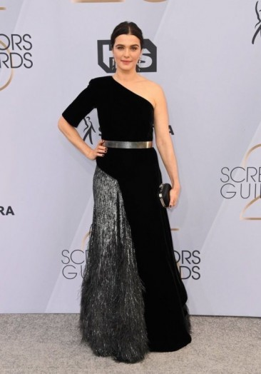 Rachel Weisz at the 2019 SAG Awards wearing a black and silver fringed one-shoulder Givenchy Haute Couture gown. This glamorous look was finished off with a metallic belt, a box clutch and Cartier jewels.