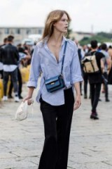 Casual street style…blue pinstripe shirt, half tucked in, black trousers and small crossbody bag