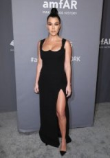 Kourtney Kardashian in a black sleeveless Versace gown with thigh high slit and black point toe courts attending the AmfAR New York Gala, 6 February 2019. Celebrity gowns ~ red carpet fashion
