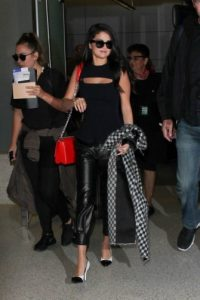 Selena Gomez arrives at LAX airport, wearing a sleeveless rib knit top with front cut out, black leather trousers, monochrome pumps and carrying a red shoulder bag, 29 September 2015. Celebrity travel style | star fashion | outfit inspiration