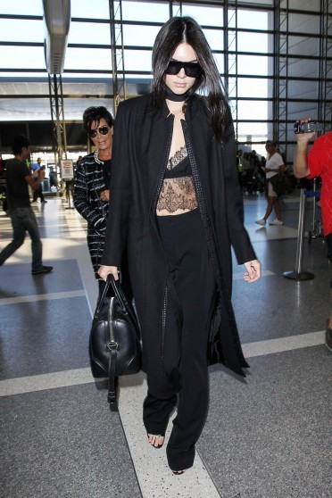 Kendall Jenner looking chic in black, wearing a lace bralet, long coat and a pair of classic style trousers, at Charles de Gaulle airport in Paris, 29 September 2015. Celebrity fashion | travel style | outfits