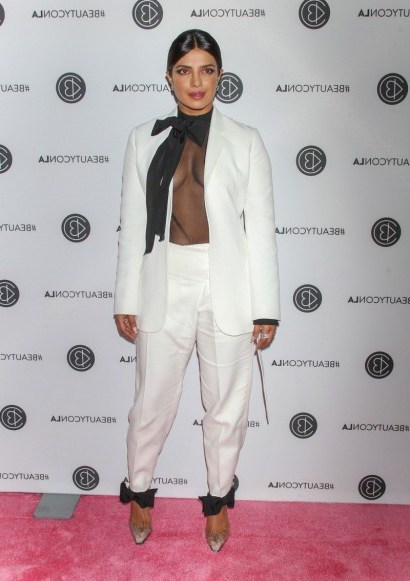 Priyanka Chopra in a white trouser suit and sheer black pussy bow blouse attending an event in LA, August 2019 – celebrity fashion USA - flipped