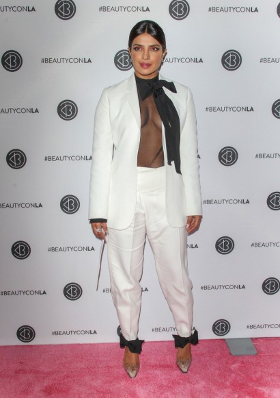 Priyanka Chopra in a white trouser suit and sheer black pussy bow blouse attending an event in LA, August 2019 – celebrity fashion USA