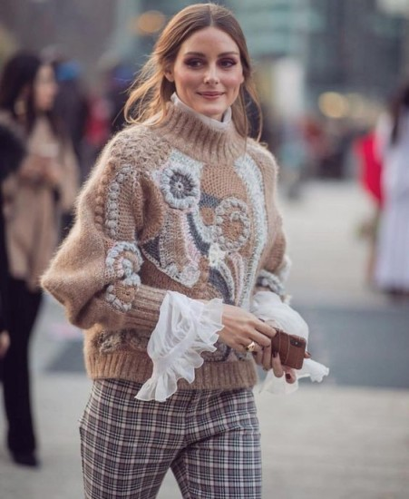 Olivia Palermo looks stunning in this bold patterned sweater, worn over a white organza blouse and checked pants
