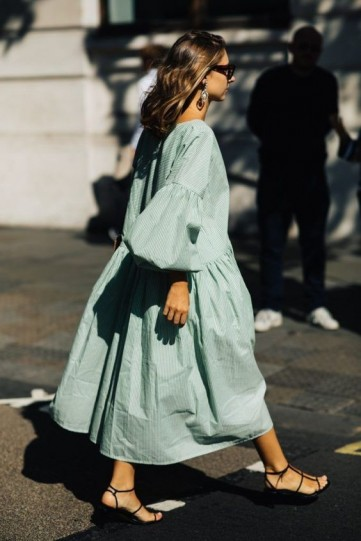 Voluminous sage green drop waist dress and black strappy heels