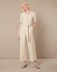 VOLUME SLEEVE JUMPSUIT – Jaeger – A lightweight and breathable option in a neutral colour, this jumpsuit is a timeless choice with a flattering cinched waist and playful voluminous sleeves. The V-neckline lends sophistication while the buttons down the front add texture and detail to the unfussy finish.