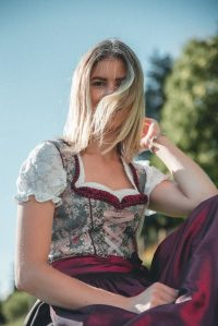 Wind swept blonde hair wearing a maroon and white floral dress
