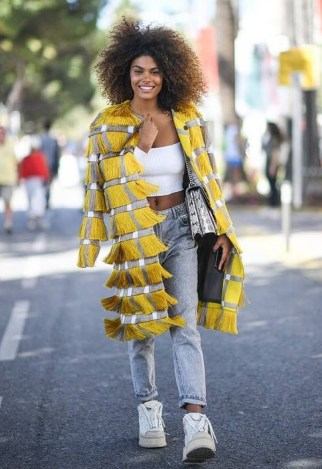 Grey straight leg jeans, white crop top and yellow fringed coat | inspirational street style looks | outfits with denim - flipped