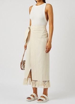 NANUSHKA Randi cream tasselled cotton wrap skirt – asymmetric side tie summer skirts with fringed hem - flipped