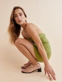 REFORMATION Dani Asymmetrical Block Heel Sandal in Gold Black / chic and shiny skinny strap sandals